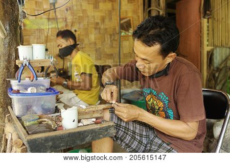 SUMATRA ISLAND INDONESIA - AUGUST 152012: Men make wooden ornaments in their workshop