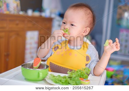 Cute funny little Asian 20 months toddler baby boy child sitting in high chair eating saladHealthy nutrition and Bio vegetable as solid food for infant. Kid eat vegetables Eating healthy concept