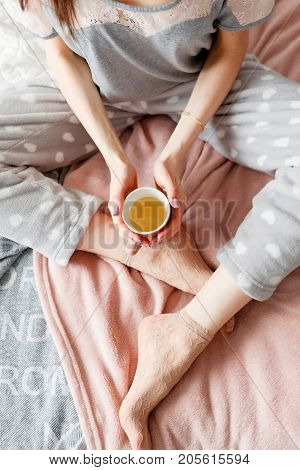 Sensual young woman sits in bed and tenderly holds cup of tea. Every morning ritual for good start of the day. Thoughtfulness and calmness, relaxation and perception concept, top view