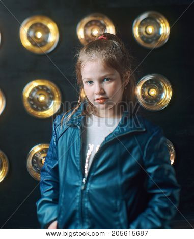 Modern little girl in a leather jacket posing on a glowing background