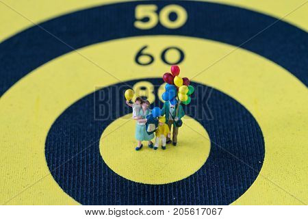 miniature happy family holding balloons standing at center of dartboard as goals or target concept.