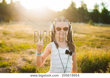 little girl in red sunglasses having fun on nature, beautiful child with black and silver headphones listening music and making gesture peace