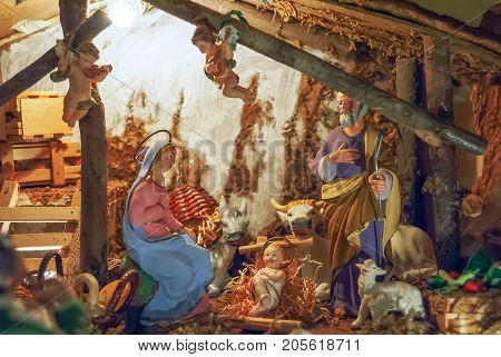 christmas nativity scene with colored figures in the manger