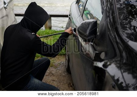 Robber man in black hoodie jacket and mask using a crowbar on his hand to break into the vehicle. Car thief or theft concept