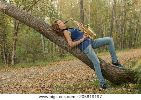 Beautiful girl with curly hair in a blue t-shirt playing the saxophone in gold on a background of nature
