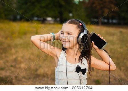 active girl with long hair having nice weekend outdoor, little girl with black and silver headphone listening song on yard