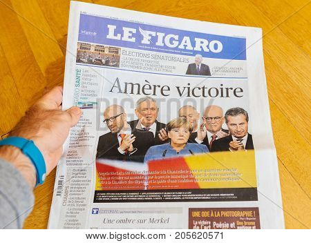 PARIS FRANCE - SEP 25 2017: Sad winning Le figaro International newspaper with portrait of Angela Merkel after election in Germany for the Chancellor of Germany the head of the federal government