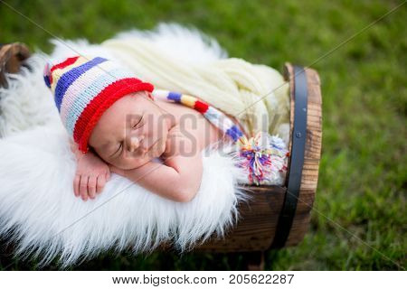 Little Sweet Newborn Baby Boy, Sleeping In Crate With Knitted Pants And Hat In Garden