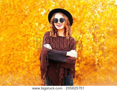 Fashion Autumn Smiling Woman In Black Round Hat, Knitted Poncho On A Yellow Leaves Background