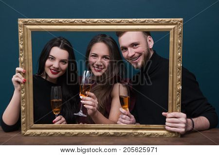 Friendship celebration. Happy portrait photoshoot. Birthday party with champagne, live picture in rectangle frame. Joyful smiling company on blue background, happiness concept