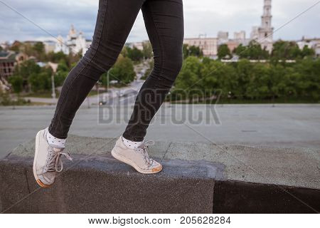 Jumping legs on urban city background. Dreamy and infantile personality, airiness and hope, fly to dreams and rich imagination concept, free space on right