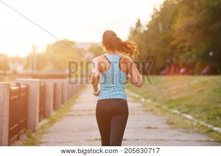 Young smiling sporty woman running in park in the morning. Fitness girl jogging in park. Rear view of sporty girl running on embankment