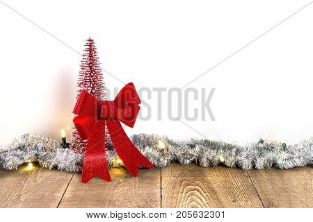 Small Sparkly Red Christmas Tree And Big Tied Bow On Rustic Wooden Table With Light And Tinsel