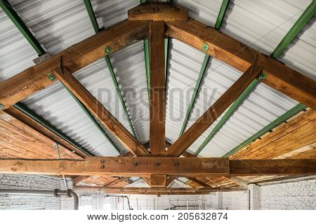 Roof of an industrial building. View from inside, rafters and wooden beams.