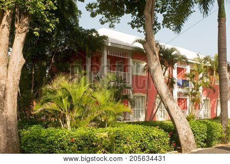 Home In The Countryside With Palm Trees, Tropical Plants And Flowers And A Bahia Grass Lawn