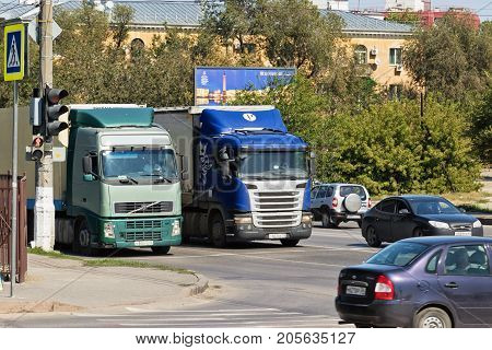 Trucks With Trailer For The Transportation Of Goods Are At The Traffic Lights With Public Transport