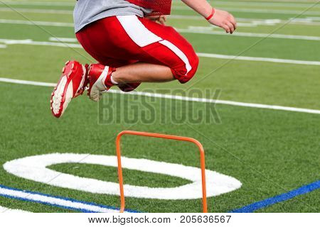 A high school football player is jumping over orange mini hurdles at practice on a green turf field.