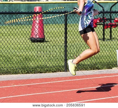 A female high school cross country runner is jumping rope on a track during practice.