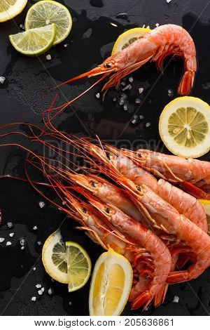 Boiled shrimps with salt and lemon on black background, copy space. Top view on appetizing seafood snack, restaurant serving.