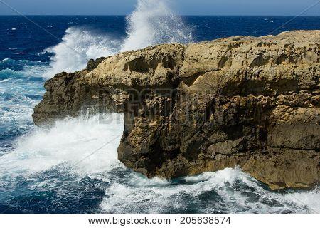 Malta, Gozo island coastline, wild waves and rocks, blue sky - sea horizon