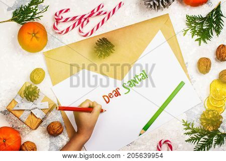 Little girl writting a letter to Santa Claus at Christmas. Happy holidays concept. Copy space