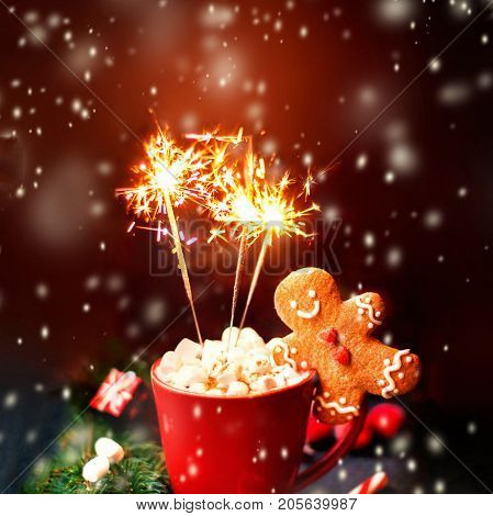 Christmas Card with hot cocoa red mug sparkling bengal fire work lights falling snow and gingerbread man cookie and festive decorations. Christmas Cozy home concept.