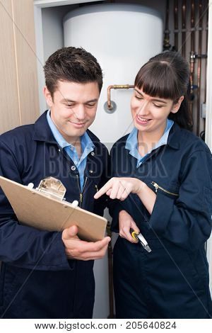 Female Trainee Plumber Working On Central Heating Boiler With Male Engineer