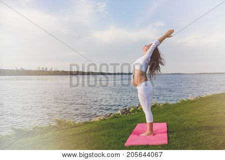 Young pregnant woman making yoga exercise and stretching outdoor. A woman standing on a yoga mat raising her hands. River in the background