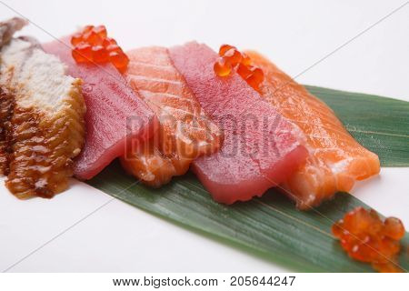 Tradional japanese food isolated at white background. Restaurant serving of fresh raw salmon, tuna and eel on bamboo leaf, closeup. Asian meals delivery