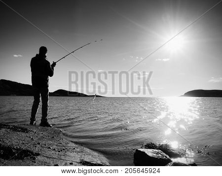 Fisherman check fishing line and pushing bait on the rod prepare himself and throw lure far into peaceful water. The adult man in warm clothes is fishing at big lake. Fisherman silhouette at sunset