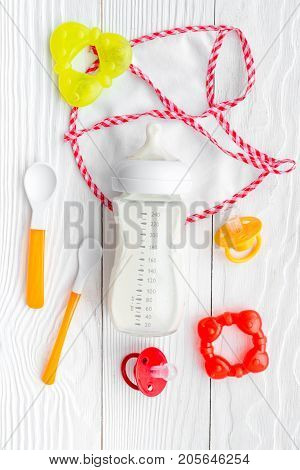 preparation of mixture baby feeding with infant formula powdered milk in bottle with bib on white wooden background top view