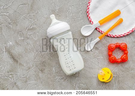 children feeding with breastmilk or infant formula powdered baby milk and toys on gray table background top view mockup