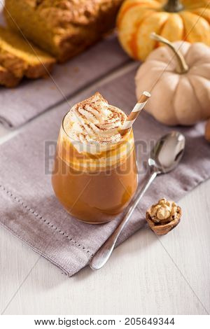 Pumpkin spice latte hot coffee drink with pumpkins whipped cream and spices