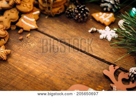 Christmas and New Year holiday background. Close up handmade ornaments, gingerbread cookiest and pine with strobila on wooden table, festive decoration concept with free space in the middle