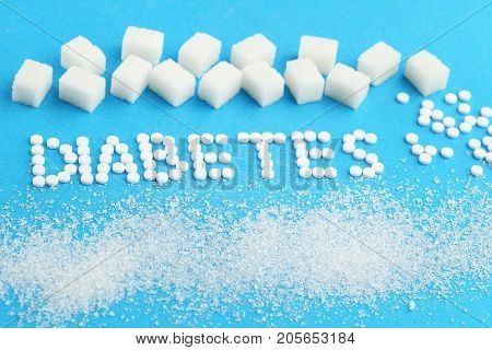 Sweetener tablets and sugar cubes with inscription Diabetes on blue background