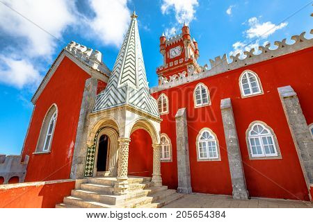 Red clock tower and rear facade of National Palace of Pena, Municipality of Sintra in Portugal.The Pena Castle is famous for its colors and different architectural styles. Sintra's main attraction