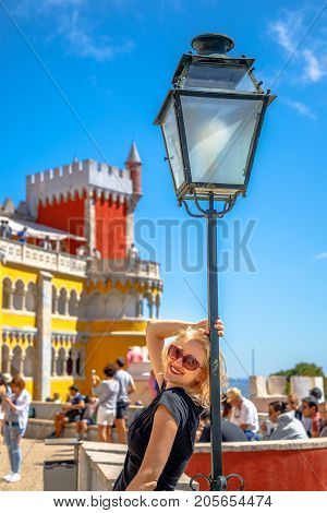 Leisure, travel and tourism concept.Happy caucasian woman posing on a light pole at colorful Pena Palace on sunny day. Pena Castle is a Unesco Heritage and most visited attraction of Sintra, Portugal.