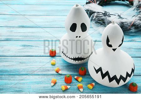 Halloween Pumpkins With Candies On Blue Wooden Table