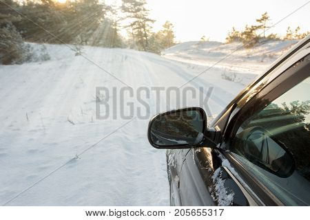 A black cars left mirror during winter on a snowy road