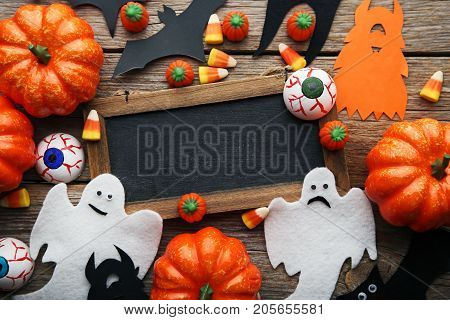 Halloween candy corns with wooden frame on grey table