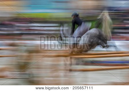 Abstract image with a moving rider and horse at show jumping on blurred background.