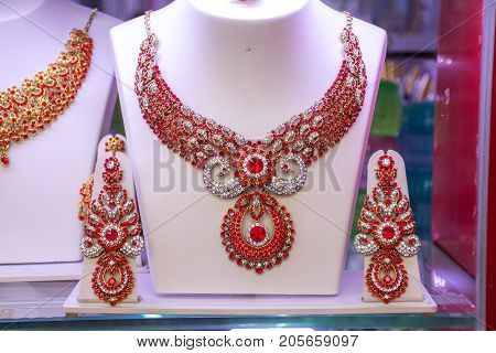 A beautiful golden red jewelry. Necklace with earrings in the shop window of the jewelry store.