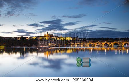 Dusk panorama of the Charles Bridge and Prague Castle Hradcany during the evening. Blue hour sky lights from lanterns. Reflection of the bridge in the water. River Vltava Prague Czech Republic