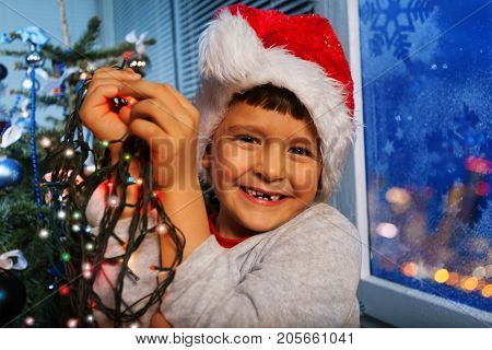 Portrait of little boy laughing smiling and holding New Year illumination lights about to put them on Christmas tree