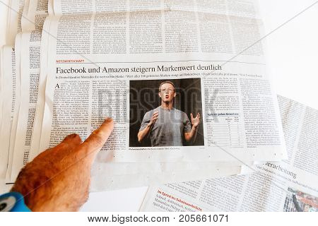 PARIS FRANCE - SEP 25 2017: Man reading international newspaper about Mark Zuckerberg Facebook CEO intention to sell 18% of social network stocks