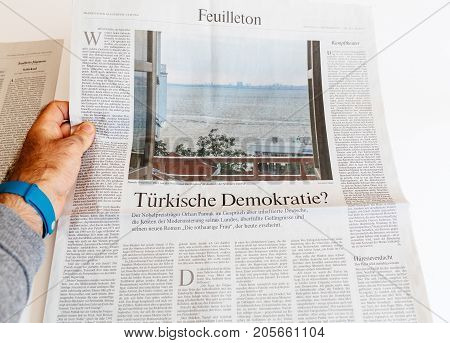 PARIS FRANCE - SEP 25 2017: Man reading German newspaper article about Turkish Democracy? by Orhan Pamuk