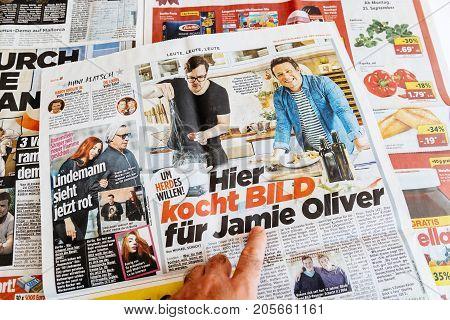 PARIS FRANCE - SEP 25 2017: Man reading Die Bild newspaper article about Jamie Oliver