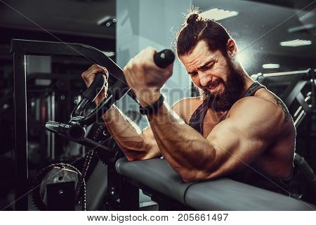 Bearded Man Doing Heavy Weight Exercise For Biceps On Machine In A Gym