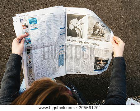 PARIS FRANCE - SEP 25 2017: Woman reading international newspaper about Irving Penn exibition at Grand Palais in Paris France