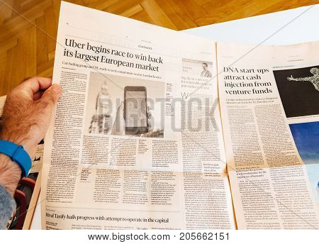 PARIS FRANCE - SEP 25 2017: Man reading international newspaper Financial Times article about Uber begins race to win back its largest European Market - London United kingdom